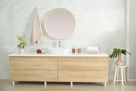 Okrągłe lustro nad umywalką w stylowym wnętrzu łazienki