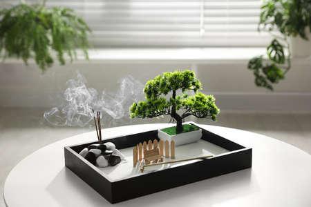 Schöner Miniatur-Zen-Garten mit Räucherstäbchen auf dem Tisch drinnen Standard-Bild