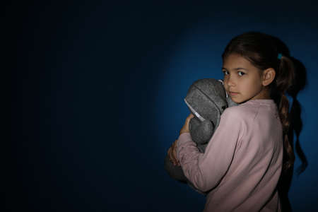 Sad little girl with toy near blue wall, space for text. Domestic violence concept Imagens