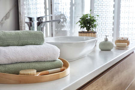 Towels and brush on table in bathroom. Space for text
