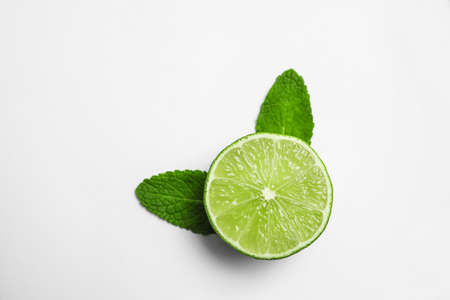 Cut fresh juicy lime and mint on white background, top view