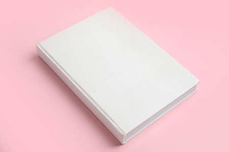 Boek met blanco omslag op roze achtergrond Stockfoto