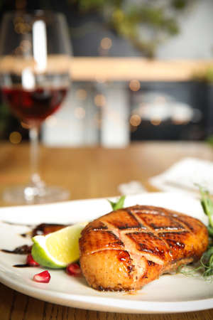 Delicious grilled duck breast served on wooden table indoors, closeup. Space for text