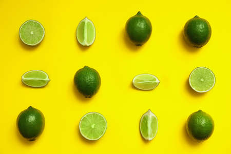 Flat lay composition with fresh juicy limes on yellow background