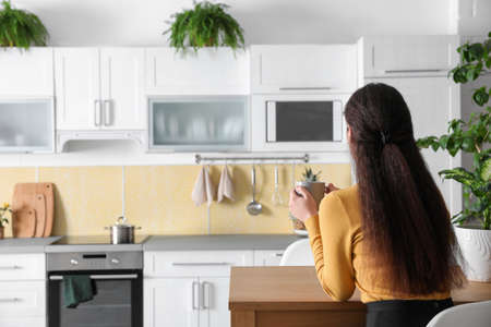Woman with drink at table in kitchen decorated with plants. Home design