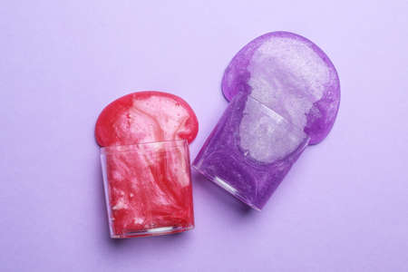 Overturned plastic containers with bright slimes on violet background, top view
