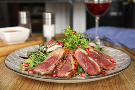 Delicious salad with roasted duck breast served on wooden table indoors
