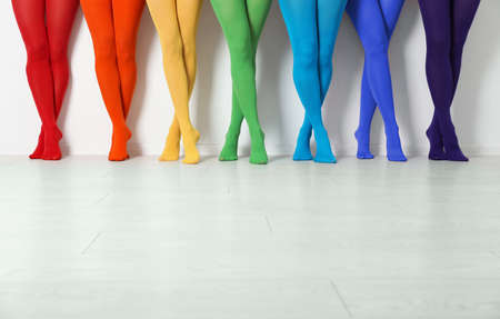 Women wearing colorful tights near white wall, closeup Stock Photo