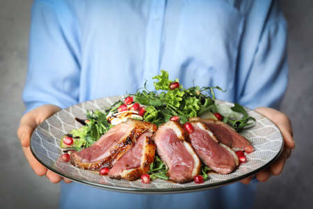 Woman holding plate with roasted duck breast on grey background, closeup
