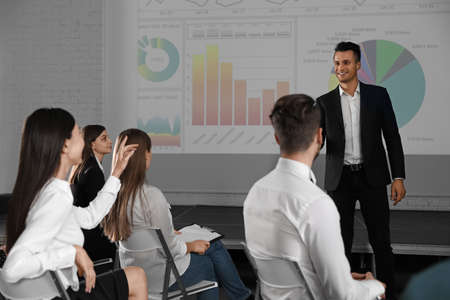Male business trainer giving lecture in conference room with projection screen Фото со стока