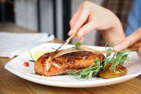 Woman eating delicious grilled duck breast served at wooden table, closeup Stok Fotoğraf