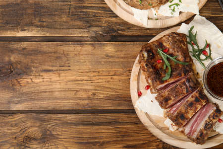 Delicious grilled ribs served on wooden table, flat lay. Space for text