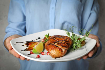 Woman holding plate with grilled duck breast on grey background, closeup