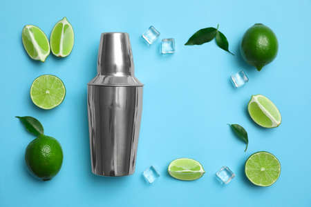 Flat lay composition with fresh juicy limes, ice cubes and cocktail shaker on light blue background. Space for text