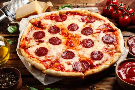 Pizza de pepperoni deliciosa caliente en mesa de madera
