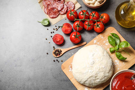 Flat lay composition with dough and ingredients on grey table, space for text. Pepperoni pizza recipe Archivio Fotografico