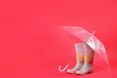 Transparent umbrella and colorful rubber boots on red background. Space for text