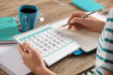 Woman making schedule using calendar at wooden table, closeup