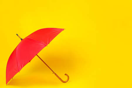 Beautiful red umbrella on light yellow background. Space for text Zdjęcie Seryjne