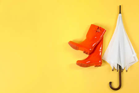 Beautiful white umbrella and red rubber boots on light yellow background, flat lay. Space for text Zdjęcie Seryjne