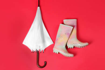Beautiful white umbrella and colorful rubber boots on red background, flat lay
