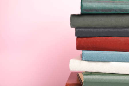Collection of old books on pink background, space for text