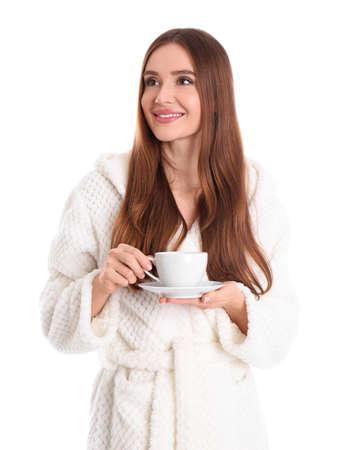 Junge Frau im Bademantel mit Tasse Getränk auf weißem Hintergrund
