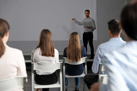 Male business trainer with laptop giving lecture in conference room with projection screen