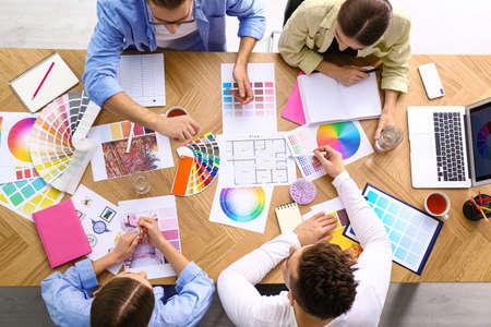 Profesjonalny zespół projektantów wnętrz pracujących przy stole, widok z góry