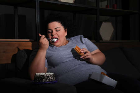 Depressed overweight woman eating sweets in living room at night
