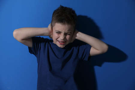 Scared little boy closing his ears near blue wall. Domestic violence concept