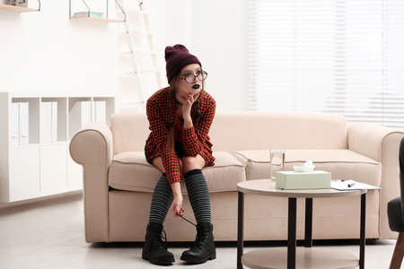 Teenage girl sitting on sofa in psychotherapist office Stock Photo