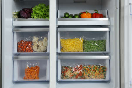 Open refrigerator with different vegetables, closeup view