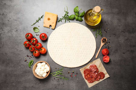 Flat lay composition with base and fresh ingredients for pepperoni pizza on grey table