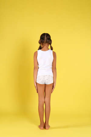 Little girl in underwear on yellow background, back view