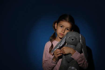 Trauriges kleines Mädchen mit Spielzeug in der Nähe der blauen Wand, Platz für Text. Konzept häuslicher Gewalt