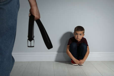 Man threatening his son with belt indoors. Domestic violence concept
