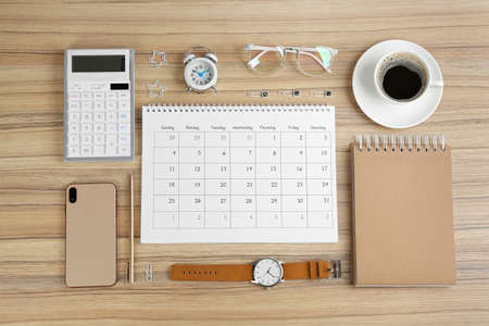Flat lay composition with calendar on wooden table