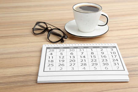 Paper calendar, cup of coffee and glasses on wooden table Reklamní fotografie