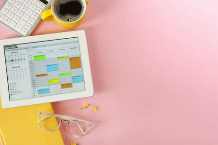 Modern tablet with calendar app on pink background, flat lay. Space for text Reklamní fotografie