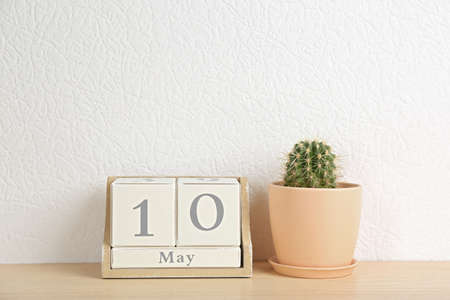 Wooden block calendar and cactus on table near white wall