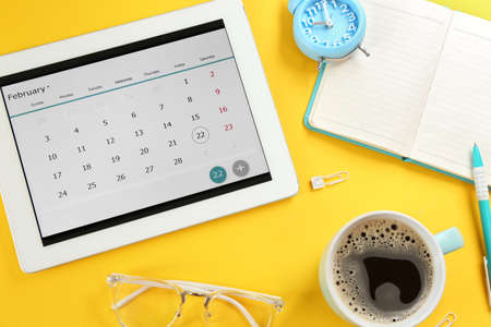Modern tablet with calendar app on yellow background Reklamní fotografie