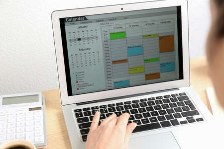 Woman using calendar app on laptop in office, closeup