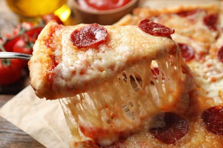 Taking slice of tasty pepperoni pizza on wooden table, closeup Фото со стока