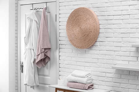 Soft comfortable bathrobe and towel hanging on door in stylish room interior