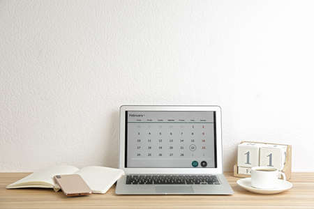 Modern laptop with calendar app in office