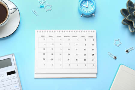 Flat lay composition with calendar on light blue background