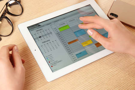 Woman using calendar app on tablet in office, closeup