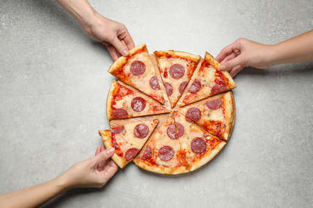 People taking slices of tasty pepperoni pizza at light grey table, top view