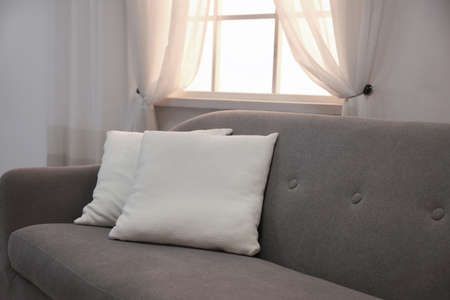Modern comfortable sofa with pillows near window indoors. Stylish interior